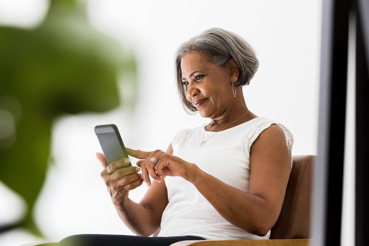 senior Black woman takes a call on her smartphone